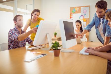 oficina: Equipo de negocios atento que trabaja en las computadoras port�tiles en una oficina brillante