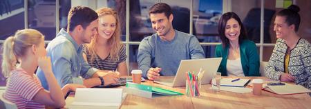 profesiones: Grupo de jóvenes colegas usando la computadora portátil en la oficina
