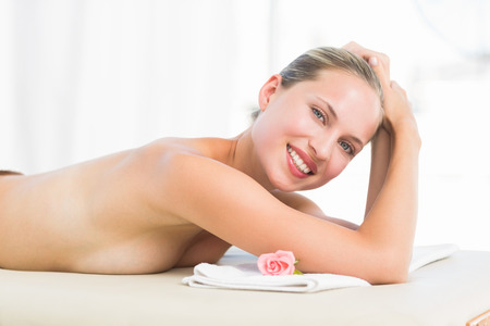 health fair: Peaceful blonde lying on towel smiling at camera at the health spa Stock Photo