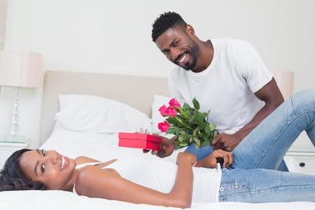 hombre romantico: Hombre rom�ntico regalar rosas a pareja en su casa en el dormitorio Foto de archivo