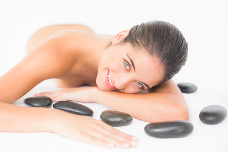 hot stones: Pretty woman enjoying lying nearby hot stones at the health spa
