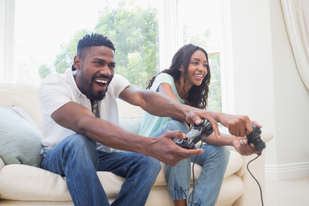 leisure game: Happy couple on the couch playing video games at home in the living room
