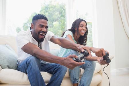 Pareja feliz en los videojuegos sofá jugando en casa en la sala de estar