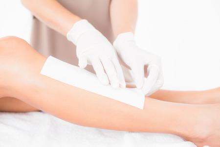 piernas hombre: Mediados de sección de terapeuta mujer depilación piernas al centro de spa Foto de archivo