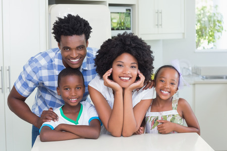Happy family smiling at camera at home in the kitchen Banque d'images
