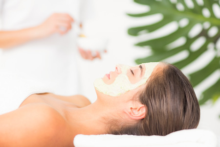 white cream: Side view of an attractive woman having white cream on her face at spa center