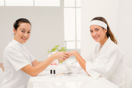 cosmetician: Close up of beautician applying nail varnish to female clients nails at spa beauty salon Stock Photo