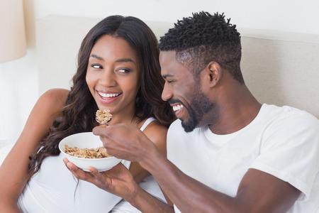 pareja comiendo: Pareja relajada en la cama comiendo cereales en el país en el dormitorio Foto de archivo