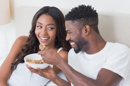 happy eating: Relaxed couple in bed together eating cereal at home in bedroom