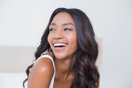 happy black woman: Beautiful woman smiling on bed at home in bedroom
