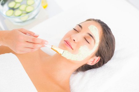 therapy room: Beautiful brunette getting a facial treatment at the health spa