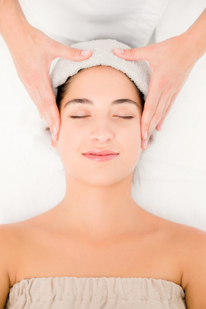 facial spa: High angle view of an attractive young woman receiving facial massage at spa center