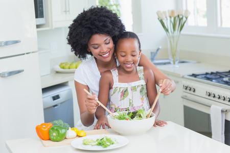 niños sanos: Madre e hija que hacen una ensalada juntos en casa en la cocina