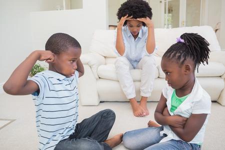combate: Viendo madre frustrada ni�os se pelean en casa en la sala de estar