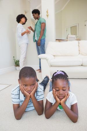 Hermanos felices sentado en el suelo utilizando el portátil en casa en la sala de estar