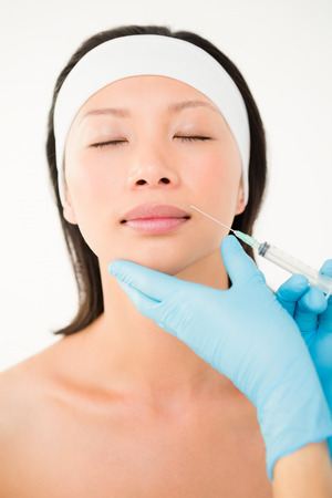 eye service: Woman receiving botox injection on her lips in medical office