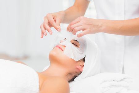 masaje facial: Hermosa morena conseguir un tratamiento facial en el spa Foto de archivo