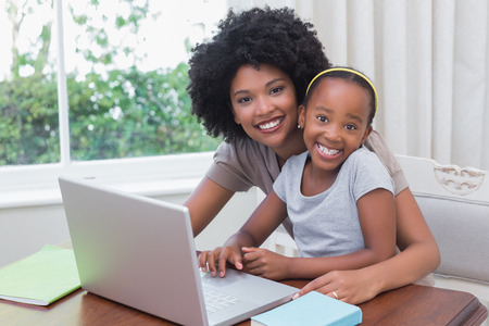 deberes: Feliz madre e hija usando la computadora portátil en casa