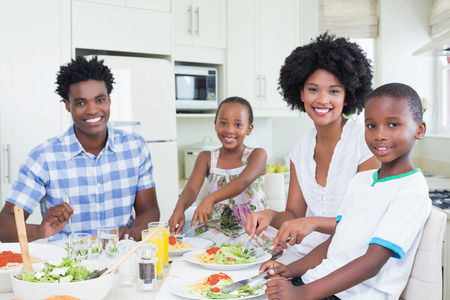 family meal: Happy family sitting down to dinner together at home in the kitchen Stock Photo