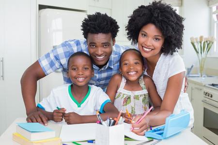 deberes: Padres felices ayudar a los niños con la tarea en casa en la cocina