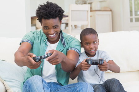 father and child: Father and son playing video games together at home in the living room
