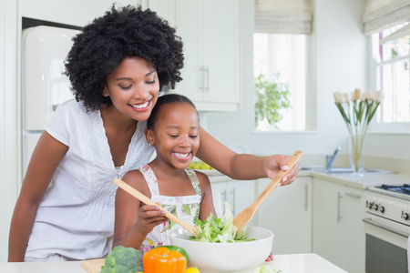 black boards: Mother and daughter making a salad together at home in the kitchen