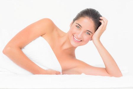 massage  table: Close up of a beautiful young woman on massage table over white background