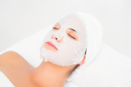 resting mask: Beautiful brunette getting a facial treatment at the health spa