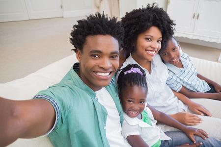 parejas felices: Familia feliz que toma un selfie en el sof� en casa en la sala de estar
