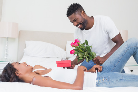 hombre romantico: Romantic man giving roses to partner at home in bedroom