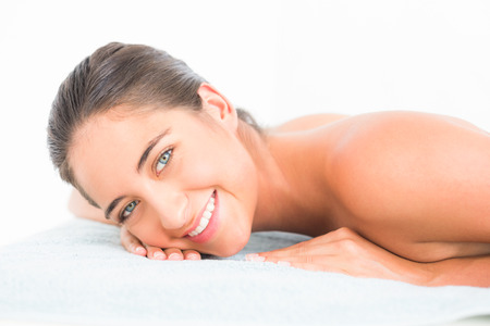 20s naked: Beautiful brunette lying on massage table smiling at camera at the health spa Stock Photo