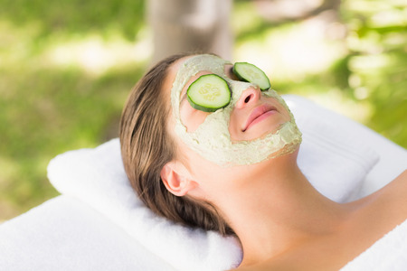 cucumbers: Attractive woman having cucumber on her face at spa center Stock Photo