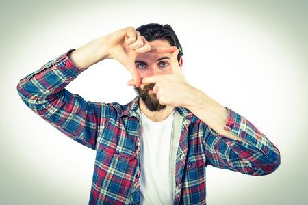 framing: Handsome hipster framing with hands on vignette background
