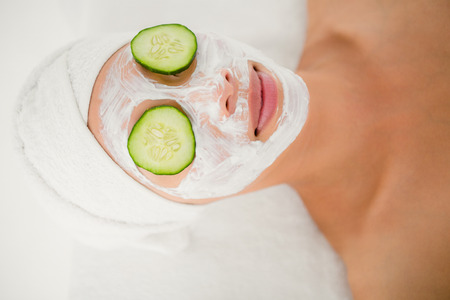 creamed: Relaxed woman with cucumber on a creamed face at the health spa