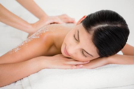 scrub: Woman enjoying a salt scrub massage at the health spa