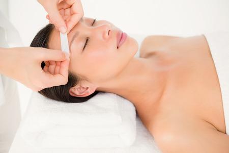 Close up view of hands waxing beautiful womans eyebrow Banco de Imagens
