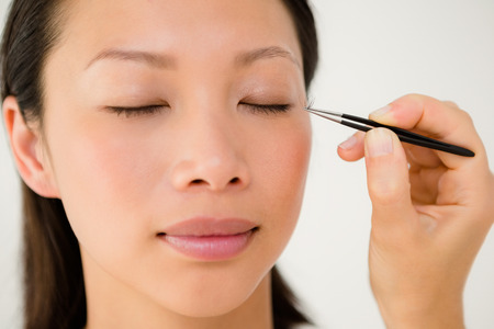 by placing: Close up view of woman placing fake eyelash on a patient at the spa health