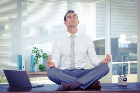 workplace wellness: Zen businessman doing yoga meditation on the desk Stock Photo
