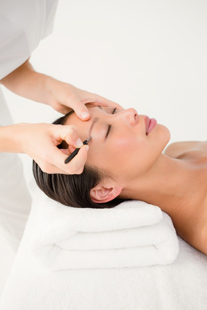 personal grooming: Woman using tweezers on patient eyebrow at the health spa