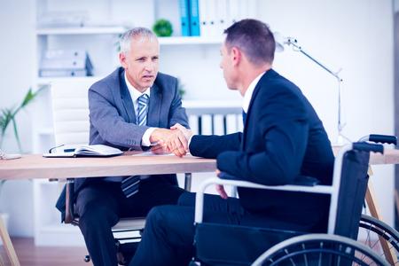 paraplegico: Hombre de negocios en silla de ruedas hablando con su colega en la oficina
