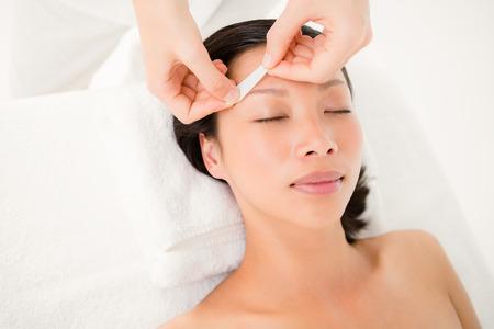 depilacion con cera: Cierre de vista de manos depilación ceja hermosa mujer