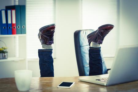 cabeza abajo: El hombre de negocios al revés en su escritorio en su oficina Foto de archivo
