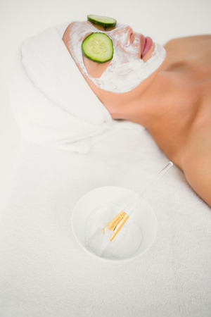 creamed: Side view of relaxed woman with cucumber on a creamed face at the health spa