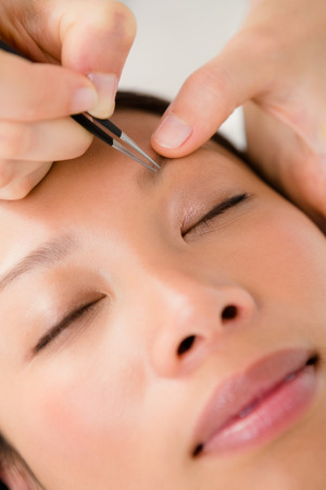 personal grooming: Close up view of woman using tweezers on patient eyebrow at the health spa Stock Photo
