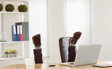 cabeza abajo: Empresario boca abajo en su escritorio en su oficina Foto de archivo