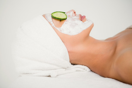 creamed: Close up view of relaxed woman with cucumber on a creamed face at the health spa
