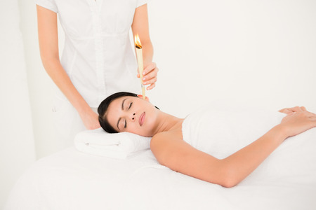by ear: Close up of a beautiful woman receiving ear candle treatment at spa center Stock Photo