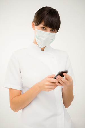 surgical mask woman: Portrait of a nurse using her mobile phone on white background