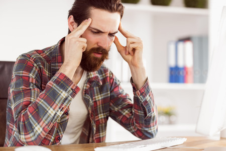 office desk: Hipster businessman stressed at his desk in his office Stock Photo