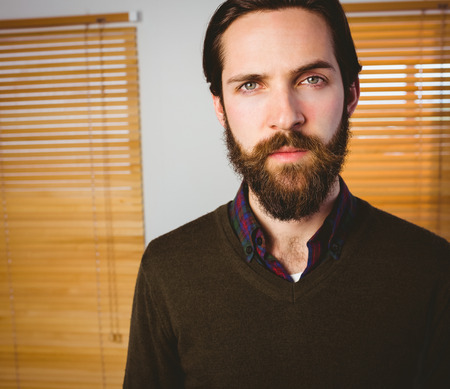 frowning: Hipster businessman frowning at camera in his office